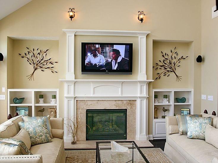 Дизайн зала с телевизором над камином