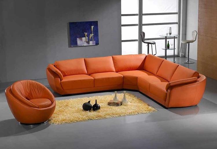 Угловой оранжевый диван в серой гостиной