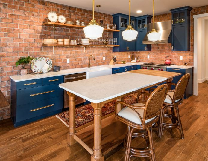 Синий кухонный гарнитур на фоне кирпичных стен
