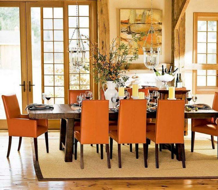 Обеденный стол в окружении рыжих стульев на фоне нейтральных обоев