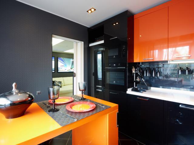 Стены серого цвета в дополнение к черно-манговому современному кухонному гарнитуру