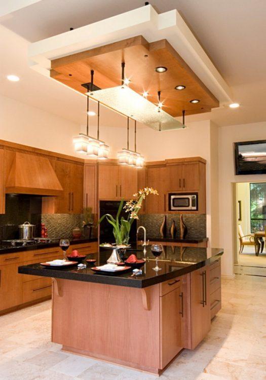 Просторная кухня с натяжным потолком с морковной вставкой над обеденной зоной - в цвет гарнитура
